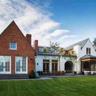 Modelo de fachada blanca, clásica, extra grande, de dos plantas, con revestimiento de ladrillo y tejado a dos aguas