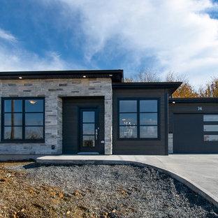 Modelo de fachada de casa negra, minimalista, pequeña, de una planta, con revestimientos combinados y tejado de teja de madera