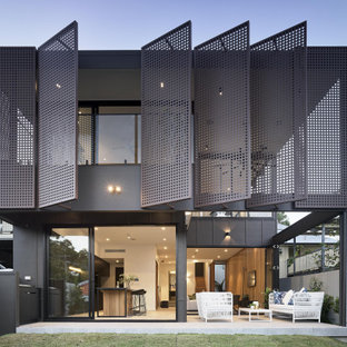 This is an example of a modern two-storey grey house exterior in Brisbane with a flat roof.
