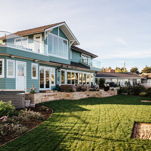 Example of a coastal green two-story mixed siding exterior home design in Sacramento with a shingle roof
