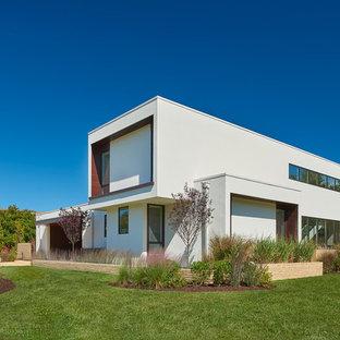 Imagen de fachada de casa blanca, moderna, grande, de dos plantas, con revestimiento de estuco y tejado plano