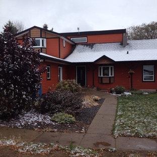Farmhouse orange two-story vinyl exterior home idea in Calgary with a shingle roof
