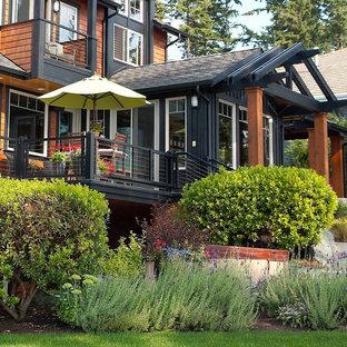 Imagen de fachada negra, rústica, de tres plantas, con revestimiento de madera
