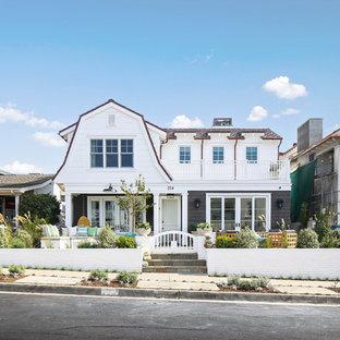 Imagen de fachada de casa blanca, marinera, de dos plantas, con revestimientos combinados y tejado a doble faldón