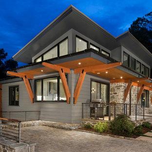 Immagine della facciata di una casa unifamiliare piccola grigia contemporanea a un piano con rivestimenti misti e tetto piano