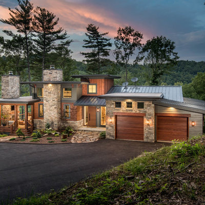 Inspiration for a large contemporary multicolored three-story mixed siding house exterior remodel in Other with a metal roof