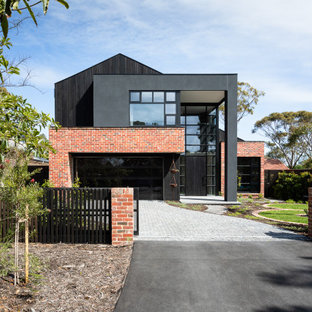 Design ideas for an industrial two-storey black house exterior in Melbourne with mixed siding and a gable roof.