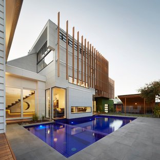 Design ideas for a contemporary two-storey white exterior in Melbourne with concrete fiberboard siding and a shed roof.