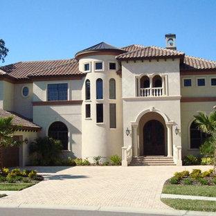 Imagen de fachada de casa blanca, mediterránea, grande, de dos plantas, con revestimiento de estuco, tejado a cuatro aguas y tejado de teja de barro