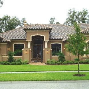 Modelo de fachada de casa marrón, mediterránea, grande, de una planta, con revestimiento de estuco, tejado a cuatro aguas y tejado de teja de barro