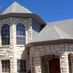 Example of a mid-sized arts and crafts beige two-story stone house exterior design in Austin with a hip roof and a shingle roof