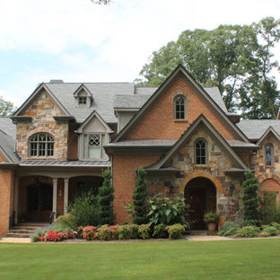 Example of a large tuscan red three-story brick exterior home design in Atlanta