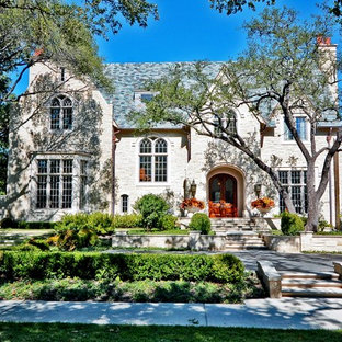 Large traditional beige two-story stone gable roof idea in Dallas with a shingle roof