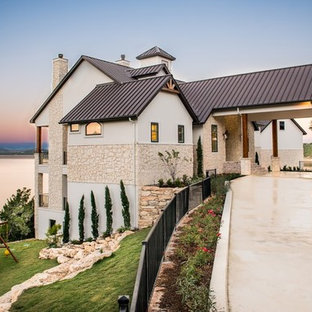 Design ideas for a country beige exterior in Houston with stone veneer and a gable roof.
