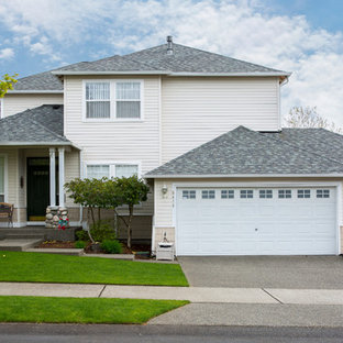 Example of a mid-sized classic beige two-story vinyl house exterior design in Other with a hip roof and a shingle roof