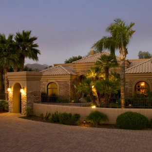 Large southwestern brown one-story brick exterior home idea in Phoenix