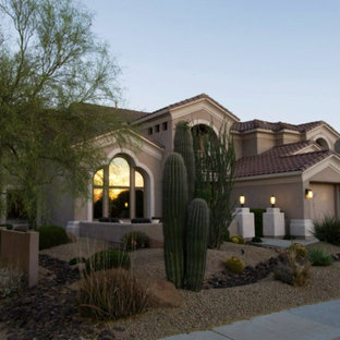 Large southwest yellow one-story stucco exterior home photo in Phoenix