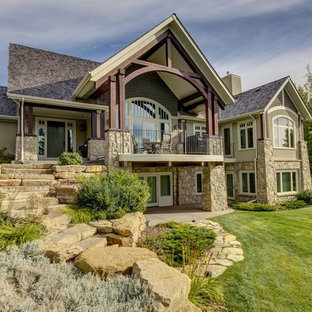 Inspiration for a timeless beige two-story stone exterior home remodel in Calgary