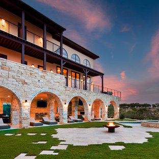На фото: большой, трехэтажный, бежевый частный загородный дом в средиземноморском стиле с облицовкой из камня, плоской крышей и крышей из гибкой черепицы