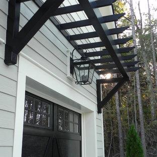 Idee per la facciata di una casa unifamiliare grigia country a due piani di medie dimensioni con rivestimento in vinile, tetto a capanna e copertura a scandole