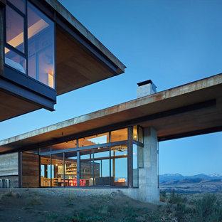 Trendy gray one-story concrete exterior home photo in Portland with a shed roof