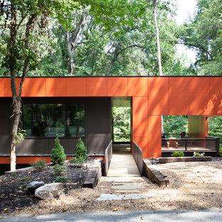 На фото: одноэтажный, оранжевый дом среднего размера в стиле модернизм с