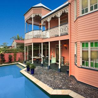 ブリスベンのヴィクトリアン調のおしゃれな二階建ての家 (寄棟屋根、戸建、金属屋根、ピンクの外壁) の写真