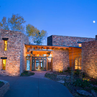 Inspiration for a large contemporary beige two-story stone exterior home remodel in Denver