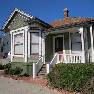 Exemple d'une façade de maison verte romantique de taille moyenne et à un étage avec un revêtement en panneau de béton fibré, un toit à deux pans et un toit en shingle.