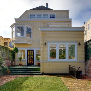 Réalisation d'une façade de maison jaune tradition à deux étages et plus.