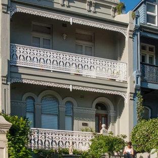 Réalisation d'une grande façade de maison de ville beige victorienne à deux étages et plus avec un revêtement en stuc, un toit plat et un toit en métal.