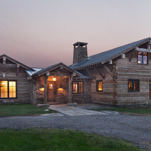Example of a mountain style brown two-story wood exterior home design in Other with a metal roof