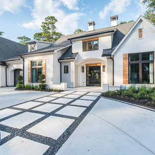 Inspiration for a large beach style white two-story brick exterior home remodel in Houston with a mixed material roof