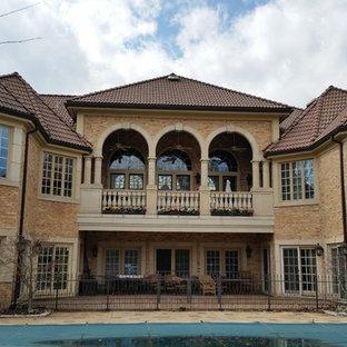 Modelo de fachada beige, mediterránea, grande, de dos plantas, con revestimiento de piedra y tejado a doble faldón