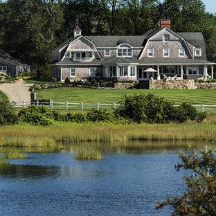 Modelo de fachada de casa beige, costera, de tamaño medio, de dos plantas, con revestimiento de madera, tejado a doble faldón y tejado de teja de madera