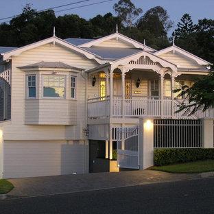 Ispirazione per la facciata di una casa grande gialla classica a due piani con rivestimento in legno