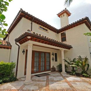 Imagen de fachada de casa beige, mediterránea, grande, de dos plantas, con revestimiento de estuco, tejado a cuatro aguas y tejado de teja de barro