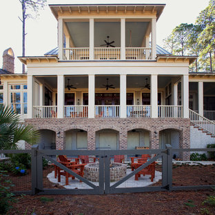 Example of a huge coastal beige three-story brick exterior home design in Charleston