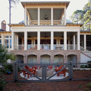 Cette image montre une très grand façade en brique beige marine à deux étages et plus.