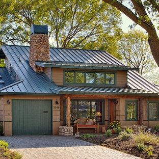 Réalisation d'une façade de maison marron chalet de taille moyenne et à un étage avec un revêtement mixte, un toit à deux pans et un toit en métal.