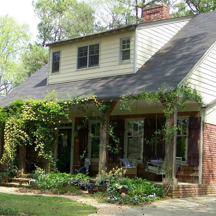 I used the existing structure of this small rancher and added a porch and upstairs area with dormers for bedrooms.  The roses at the front steps are Lady Banks because they don't have thorns; the othe