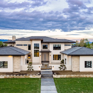 Large contemporary beige two-story mixed siding house exterior idea in Boise with a hip roof and a tile roof