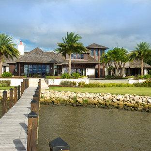 Diseño de fachada marrón, exótica, grande, de una planta, con revestimiento de madera y tejado a cuatro aguas