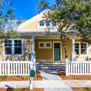 Idee per la facciata di una casa piccola gialla american style a due piani con rivestimento in legno e tetto a capanna
