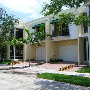 Modern inredning av ett stort gult flerfamiljshus, med två våningar, stuckatur, platt tak och tak i mixade material