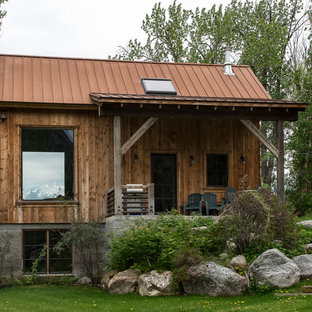 Mid-sized mountain style brown two-story wood house exterior photo in Other with a hip roof and a metal roof