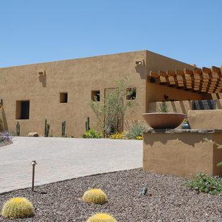 Foto på ett stort amerikanskt beige hus, med allt i ett plan, stuckatur och platt tak