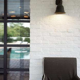 Стильный дизайн: одноэтажный, белый частный загородный дом в классическом стиле с облицовкой из крашеного кирпича, двускатной крышей и крышей из гибкой черепицы - последний тренд