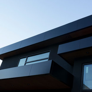Foto de fachada negra, grande, con revestimiento de metal y tejado plano