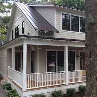 Modelo de fachada de casa beige, marinera, de tamaño medio, de dos plantas, con revestimiento de aglomerado de cemento, tejado de un solo tendido y tejado de metal